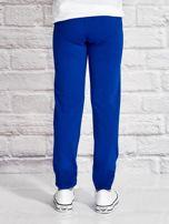 Ciemnoniebieskie spodnie dresowe dla dziewczynki z flamingiem                                  zdj.                                  2