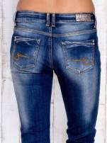 Ciemnoniebieskie spodnie dzwony jeansowe z przetarciami