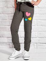 Ciemnoszare spodnie dresowe dla dziewczynki z nadrukiem serc                                  zdj.                                  1