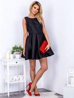 Czarna sukienka z perłowym połyskiem i kokardą                                  zdj.                                  4