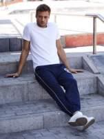 Granatowe dresowe spodnie męskie z lampasami po bokach i aplikacją                                  zdj.                                  6