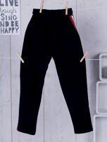 Granatowe spodnie dresowe dla dziewczynki z taśmą tricolor                                  zdj.                                  2
