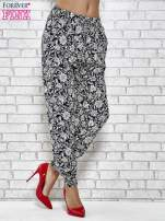 Granatowe zwiewne spodnie alladynki we wzór kwiatków                                                                          zdj.                                                                         1