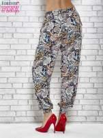 Granatowe zwiewne spodnie alladynki we wzór kwiatowy                                  zdj.                                  4