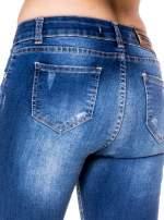 Niebieskie spodnie jeansowe rurki z rozjaśnianą nogawką i rozdarciami na kolanach                                  zdj.                                  7