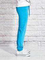 Turkusowe spodnie dresowe dla dziewczynki z nadrukiem serc                                  zdj.                                  3